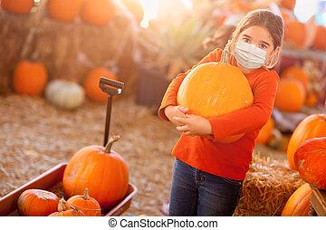 Cute Girl Choosing A Pumpkin At Pumpkin Patch Wearing Medical Face Mask
