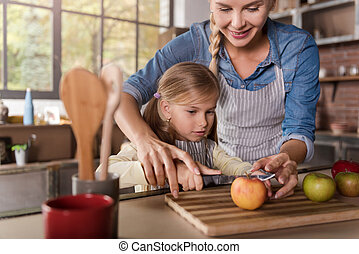 Cute girl cooking with her mother in the kitchen