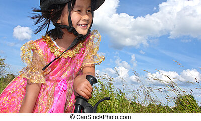 Cute girl cycling with a princess outfit