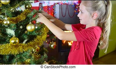cute girl decorating christmas tree next to fireplace