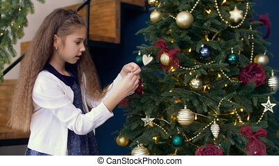 Cute girl decorating xmas tree with colorful bauble -...