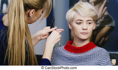 Cute girl doing makeup in the salon