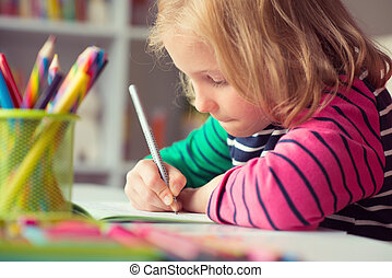 Cute pretty girl drawing with pencils at school