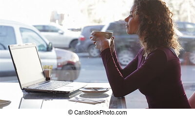 Cute girl drinking coffee on a cafe in the city
