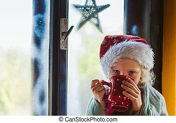 cute girl drinking hot tea by the window