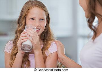 Cute girl drinking milk as she look