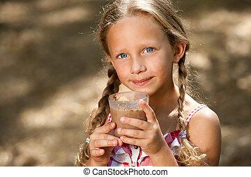 Cute girl drinking milk chocolate. - Close up portrait of...