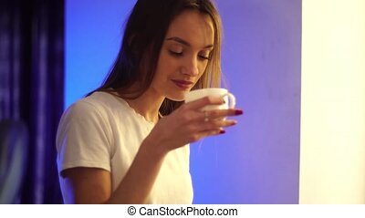 Cute girl drinks coffee and smiles