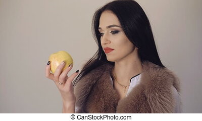 Cute girl eating a big, juicy apple, smiling and flirting on background