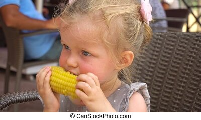 Cute girl eating boiled corn - Funny little girl sitting in...