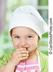 Cute girl eating delicious fresh salad in kitchen