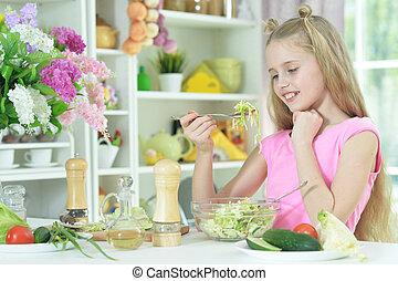 Cute girl eating delicious fresh salad