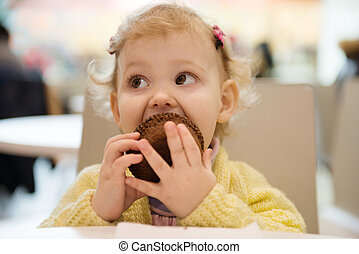 Cute girl eating muffins in cafe