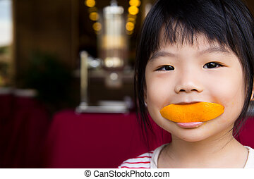 Cute girl eating orange