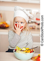 Cute girl eating tomato while cooking salad in kitchen