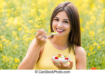 Cute girl eating yogurt with fresh fruit outdoors.