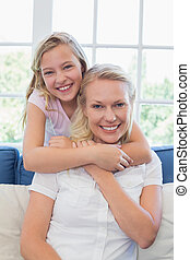 Cute girl embracing mother from behind