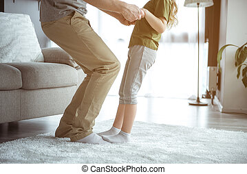 Cute girl enjoying dance with daddy in room