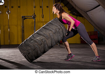 Beautiful Hispanic young woman halfway from flipping a tire in a cross-training gym