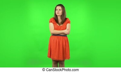 Cute girl focused thinking about something. Chubby girl in a coral dress with straight hair medium length and light eyes on green screen at studio
