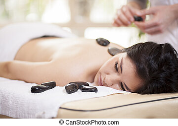 Cute girl getting a stone massage
