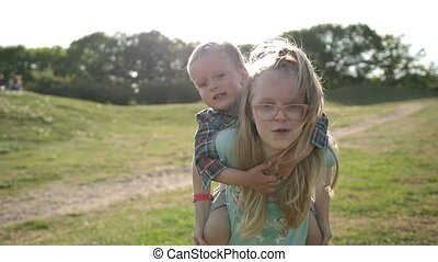 Cute girl giving toddler boy piggyback ride in park