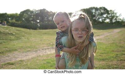 Cute girl giving toddler boy piggyback ride in park
