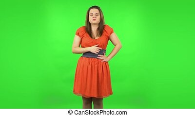 Cute girl goting a cold and sneezing. Chubby girl in a coral dress with straight hair medium length and light eyes on green screen at studio