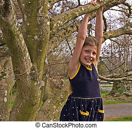 Cute Girl Hanging From Tree Branch