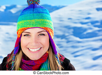 Cute girl having fun outdoor at winter mountains, closeup portrait of a beautiful smiling female face over snow, young teen tourist woman wearing colorful hat, Christmas holidays travel and vacation