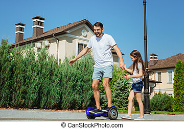 Cute girl helping her father ride hoverboard