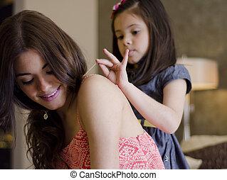 Cute girl helping mom get ready