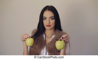 Cute girl holding a juicy green pears in hands, posing and smiling to camera 4K