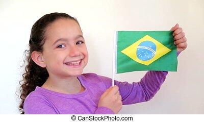 Cute girl holding flag of Brazil - Shot of Cute girl holding...