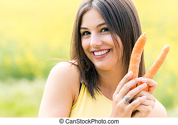Cute girl holding organic carrots outdoors.