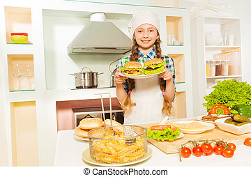 Cute girl holding plate with hamburgers at kitchen