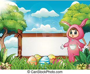 Cute girl in a pink bunny costume standing near blank sign and easter egg