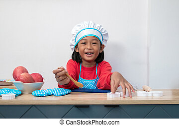 Cute girl in chef uniform and simulated cooking toys in the kitchen counter