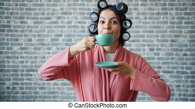 Cute girl in gown and hair rollers drinking tea smiling on...