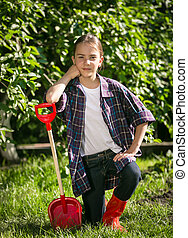 girl in gumboots posing with toy spade at garden - Cute girl...