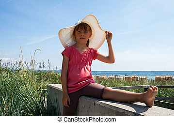 Cute girl in hat on the beach
