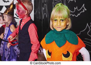 Cute girl in pumpkin costume celebrating halloween with friends