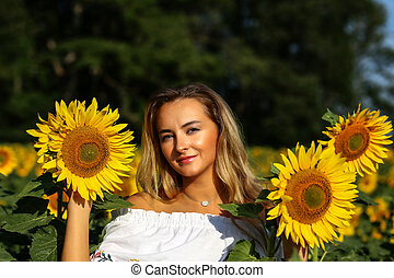 Cute girl in the field full of sunflowers