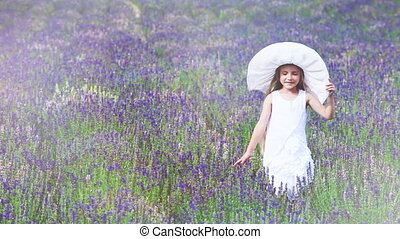 Cute girl in the hat walking on field. Child going to the camera and smiling
