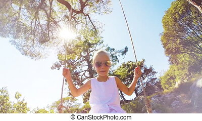 Cute girl in white dress with blond on a swing. She is happy and laughing at camera
