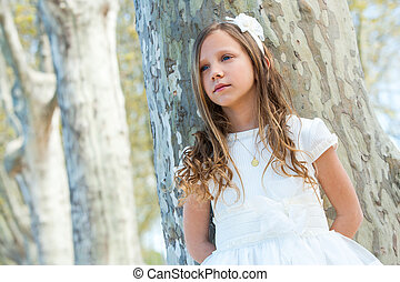 Cute girl in white dress with lost look.