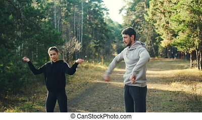 Cute girl is doing sports in park with her boyfriend warming up wrists and arms during training together on warm sunny day. Well-being and healthy hobby concept.