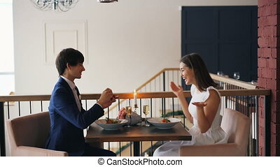 Cute girl is excited about marriage proposal smiling and laughing saying yes while her boyfriend is asking her to marry him, putting ring on her finger and kissing her hand.