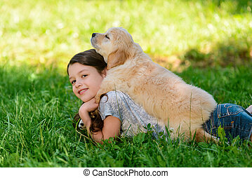 Cute girl is laying with a dog on her back on the grass