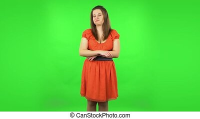 Cute girl is listening attentively and nodding her head pointing finger at viewer. Chubby girl in a coral dress with straight hair medium length and light eyes on green screen at studio